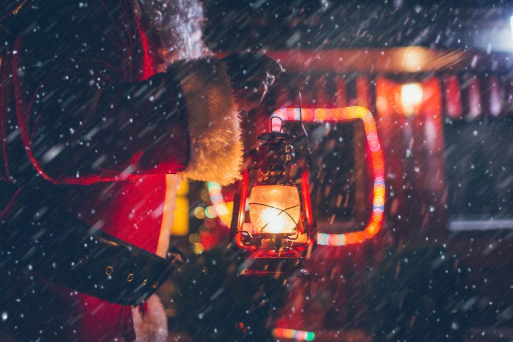 Santa Claus is lighting his way through a snowstorm