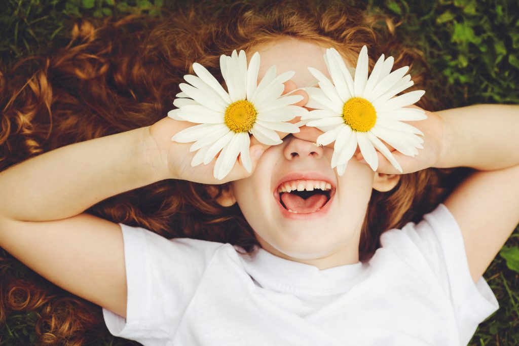 Child laying in grass with daisies on her eyes