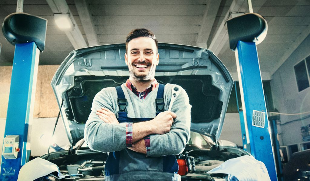 Toyota service mechanic standing in front of a Toyota vehicle